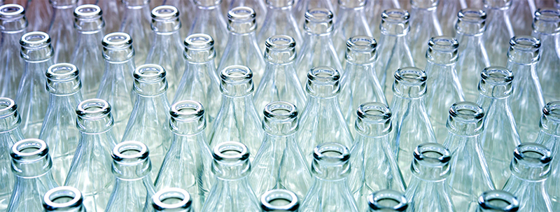 a group of empty glasses in front of a water bottle