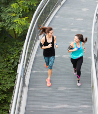 two ladies running on a bridge in a park