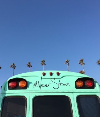 blue sky and a van with never stress written on it