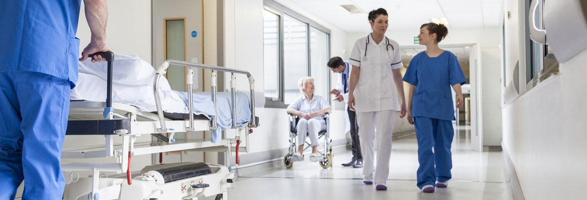 hospital staffs in blue and white uniform walking in hospital corridor