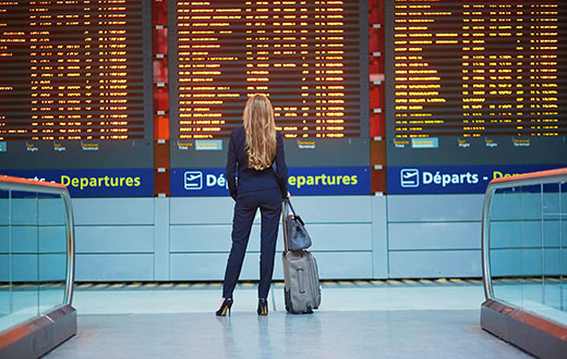 Woman looking at airport departures board