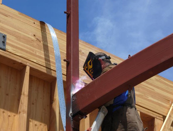 Main soldering a steel beam at construction site