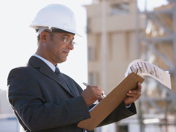 Man in hardhat reviewing documents on clipboard
