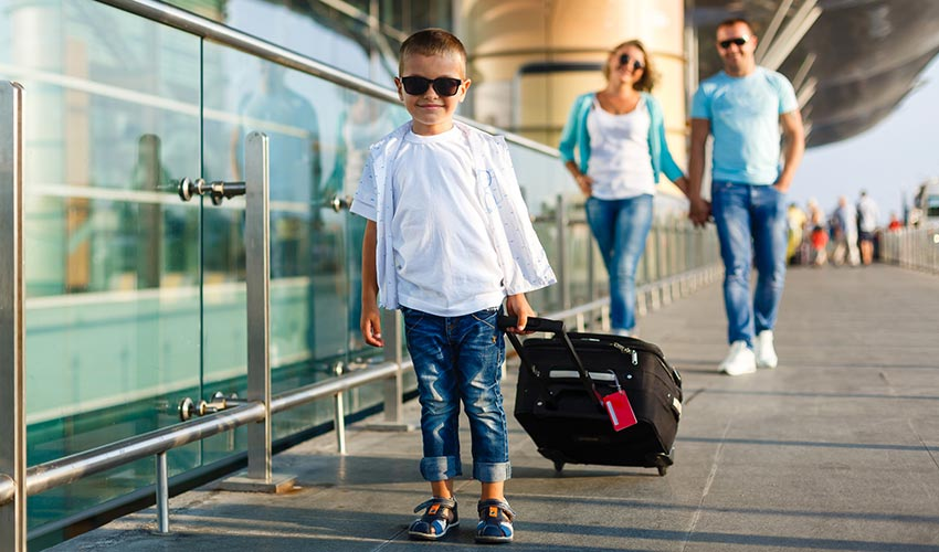 Cute-little-kid-boy-with-suitcase-on-international-airport.-Mother-and-daughter-on-background